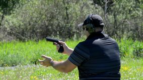 Man shoots with a gun in targets on shooting range.