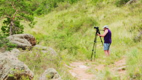 Man shoots landscape. Photographer to take pictures in the technique stock video