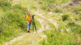Man shoots landscape. Photographer to take pictures in the technique stock video footage