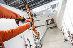 Man shoots out of the block archery. Male archer shooting in competitions of the compound bow with arrows Stock Images