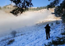 Man shoots photo of laying cloud. Man shoots photo of laying cloud on hillside of mountains with pine trees forest in Zaili Alatau rocks,  Kazakhstan Stock Photography