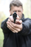 Man shoots from pistol. Royalty Free Stock Images