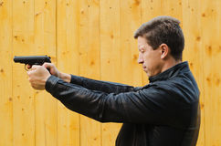 The man shoots from a pistol, having closed eyes Royalty Free Stock Images