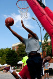 Man Shoots Reverse Layup In Outdoor Street Basketball Tournament. Athens, GA, USA - August 24, 2013:  A young man shoots a reverse layup in a 3-on-3 basketball Royalty Free Stock Image