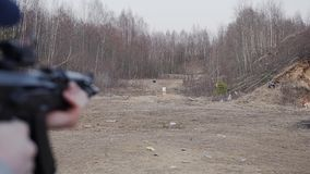 A man shoots at a target with an assault rifle at the shooting range. Move the camera from the target to the arrow stock footage