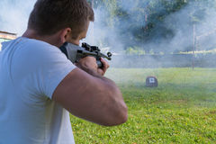 A man shoots a target from a pneumatic gun. Rear view of a man royalty free stock photography