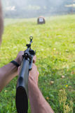 A man shoots a target from a pneumatic gun. A view from behind the shoulder Royalty Free Stock Image
