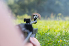 A man shoots a target from a pneumatic gun. A view from behind the shoulder Royalty Free Stock Images