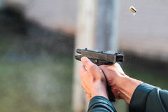 Man shoots from the weapon. Man firing a bullet from a gun. frozen bullet Stock Image