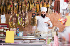 Man shop seller demonstrating jamon in shop Stock Photos