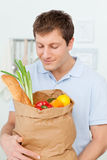 Man with shoping bags in the kitchen. At home royalty free stock photo
