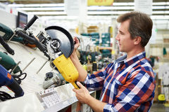 Man shopping for angle grinder in hardware store. Close-up stock photography