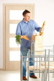 Man with shopping bag at home Stock Photo