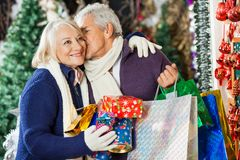 Man With Shopping Bags Kissing Woman At Store Stock Photos