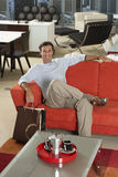 Man with shopping bags sitting on new red sofa in furniture store, smiling, portrait Stock Images