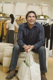 Man With Shopping Bags Sitting In Store Stock Photos