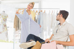 Man with shopping bags while woman selecting a dress Stock Images
