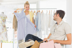 Man with shopping bags while woman selecting a dress Stock Photos