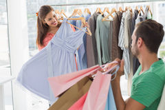 Man with shopping bags while woman selecting a dress Royalty Free Stock Photos
