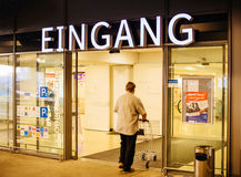 Man with shopping cart enetering Edeka store under Eingang entra. KEHL, GERMANY MAR 30, 2017: Man with shopping cart above Eingang signage translated as Entrance Stock Image