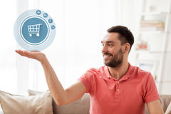 Man with shopping cart icon projection at home Stock Photography
