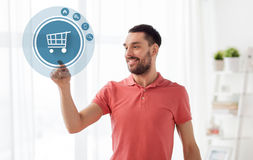 Man with shopping cart icon projection at home Stock Photo