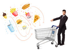 Man with shopping cart with toxic junk food. Businessman pushing a shopping cart and toxic junk food and cigarettes coming out of it Royalty Free Stock Photos