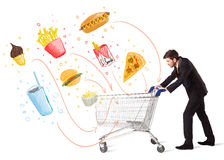 Man with shopping cart with toxic junk food. Businessman pushing a shopping cart and toxic junk food and cigarettes coming out of it Royalty Free Stock Images