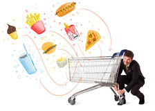 Man with shopping cart with toxic junk food Royalty Free Stock Photos