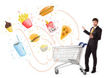 Man with shopping cart with toxic junk food. Businessman pushing a shopping cart and toxic junk food and cigarettes coming out of it Stock Photos