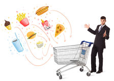 Man with shopping cart with toxic junk food. Businessman pushing a shopping cart and toxic junk food and cigarettes coming out of it royalty free stock photography