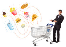 Man with shopping cart with toxic junk food. Businessman pushing a shopping cart and toxic junk food and cigarettes coming out of it Stock Photo