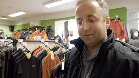 Man shopping for clothes and speaks to cashier Royalty Free Stock Image
