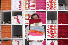 Man shopping in department store, holding large pile of folded towels, face obscured, front view, portrait, shelves in background Stock Photos
