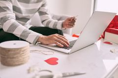 Man shopping for gift online while sitting on couch at home. royalty free stock image