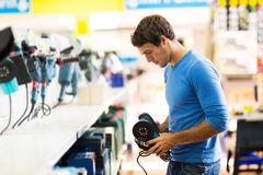 Man shopping hardware store. Handsome young man shopping for sander in hardware store Royalty Free Stock Photos