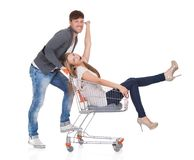 Man shopping with his wife in a trolley. Handsome young men going out to shop pushing his carefree laughing wife along in a shopping trolley or cart as they have Royalty Free Stock Images