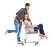 Man shopping with his wife in a trolley. Handsome young men going out to shop pushing his carefree laughing wife along in a shopping trolley or cart as they have Royalty Free Stock Image