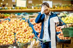 Man with shopping list in the supermarket stock photography