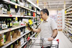 Man shopping and looking at food in supermarket. Man with cart shopping and looking at food in supermarket Royalty Free Stock Image