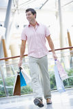 Man shopping in mall. Carrying bags Stock Image