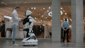 The man in the shopping Mall communicate with a robot Advisor. Modern shop and robot seller. Robot helps a man in the. Mall stock video