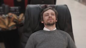 Man in shopping mall lay in massage chair close up shot stock footage