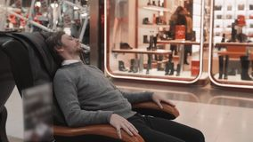 Man in shopping mall lay in massage chair close up shot stock video footage