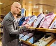 Man in a shopping mall. Middle-aged man choosing shirts in a shopping mall Royalty Free Stock Image