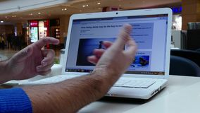 Man in shopping mall reading BBC news on laptop stock video