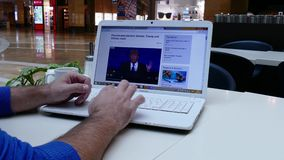 Man in shopping mall reading BBC news on laptop stock video footage