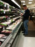 Man shopping for meat at Grocery Store. Man looking at the label on a package of meat in a grocery store royalty free stock images