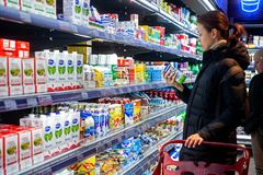 Minsk, Belarus, March 25, 2018: Man shopping milk in grocery store. Young woman reading ingredients,declaration or expiration date. Man shopping milk in grocery royalty free stock images