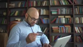 Man shopping online with credit card. Young man using credit card online with his laptop at home on the background of. The library. slow-motion. Man at home stock video